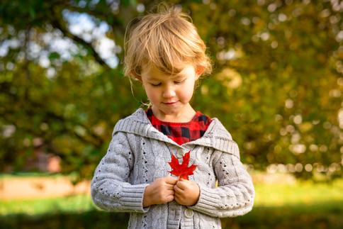 Child holding maple leaf