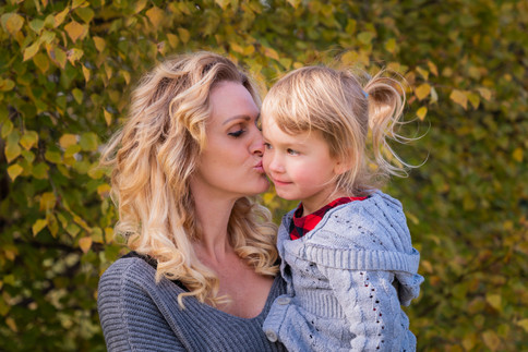 Mom kissing her daughter's cheek