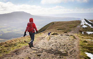 A hiker walking down from the summit of