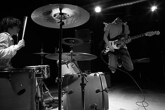 Drummer playing and a guitarist jumping
