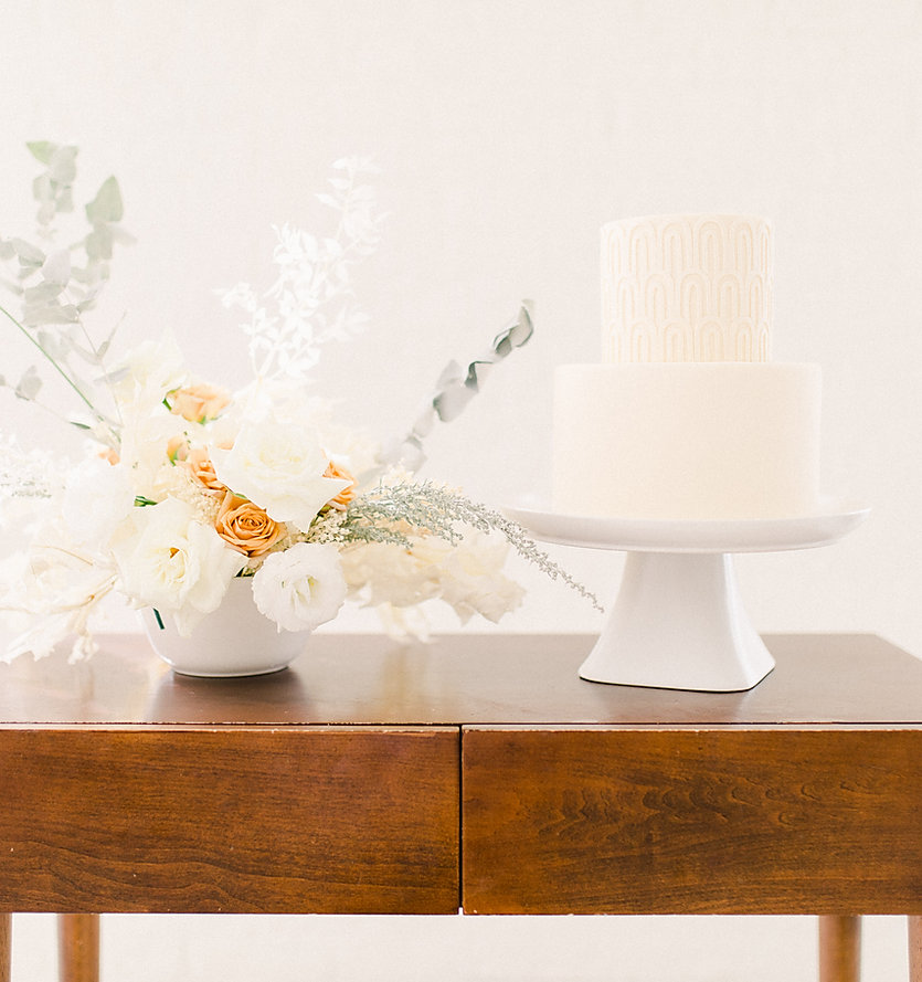 Two tiered cream fondant wedding cake with arch pattern