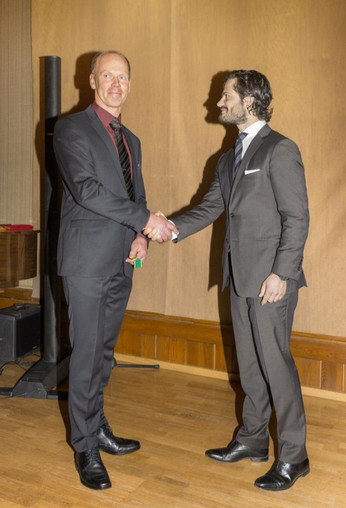 Lars tar emot gudmedalj ur Prina Carl-Philips hand.