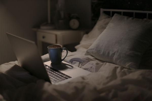 coffee mug sitting on laptop sitting on a bed