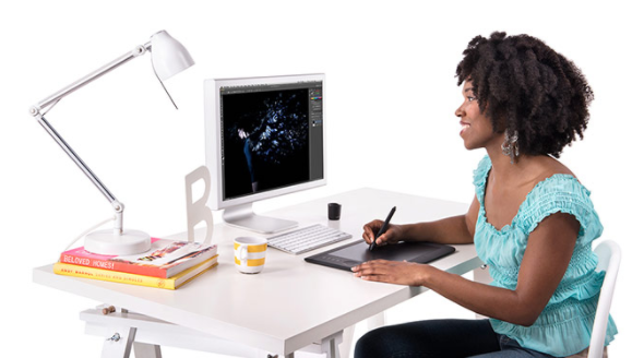 woman sitting at desk using digital drawing tablet