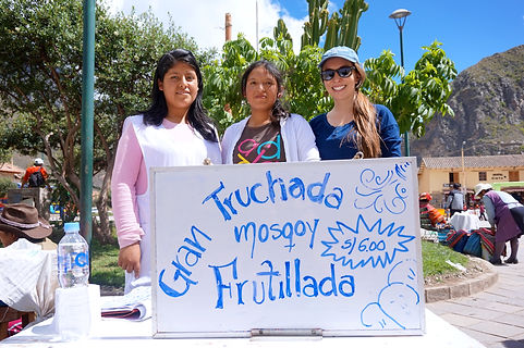 "T'ikary students volunteering with sign reading ""Gran Truchada Mosqoy Frutillada"""