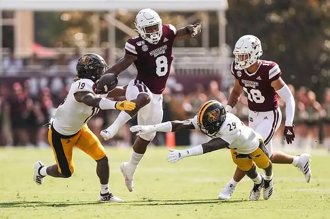 MSU running back Kylin Hill leaps two defenders