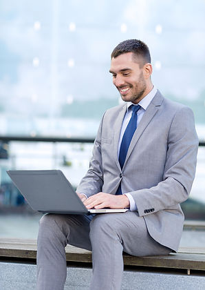Businessman with dark hair and short beard is seated outside on wood, no back support, laptop on his lap, neck flexed downward, he is wearing a grey 2 piece suit and blue tie, pale blue shirt.