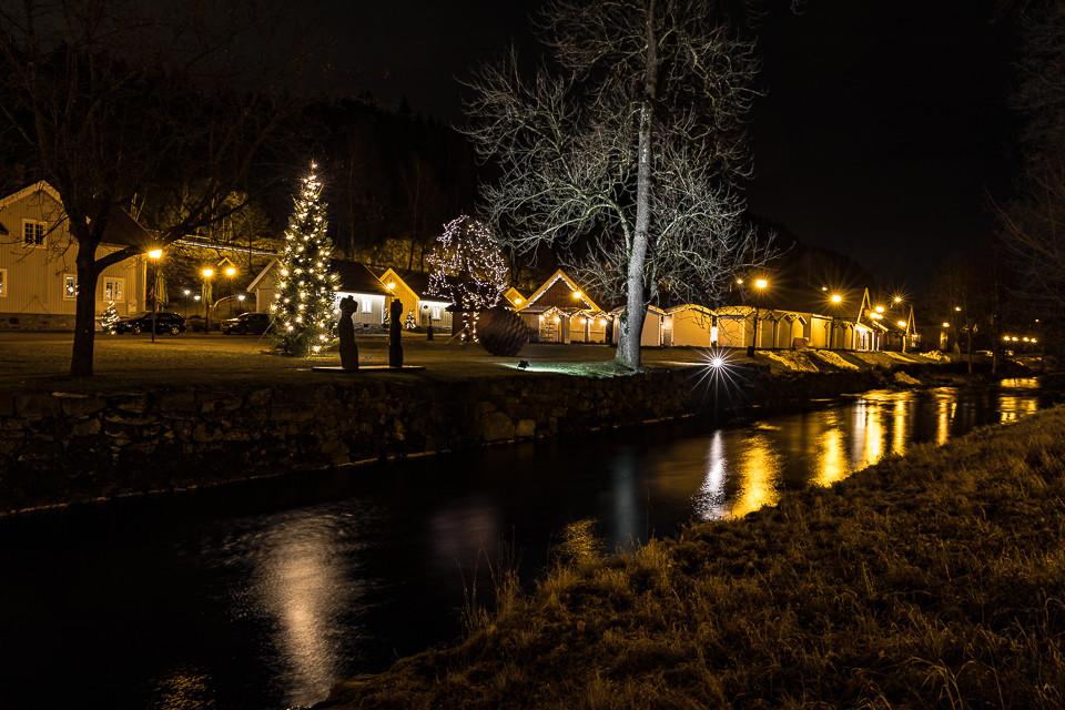 Lyset fra de gamle fredede bygningene speiler seg i vannet fra Lommedalselva