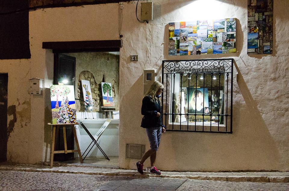 Kvinne ser på utstillingsvinduet til lite kunstgalleri i Altea