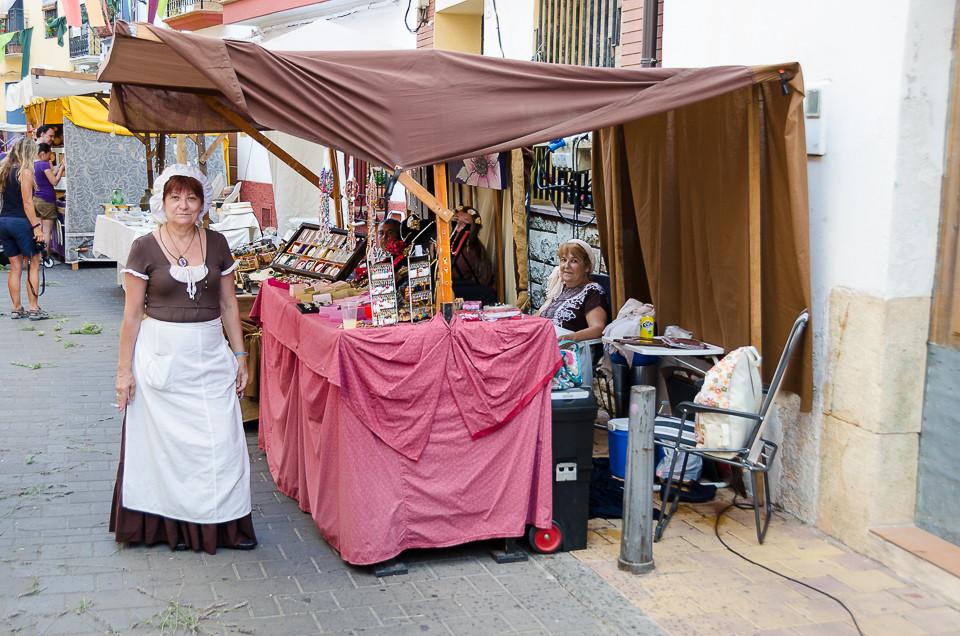 Kvinner poserer foran salgsbod på middelaldermarked i Nucia i Spania