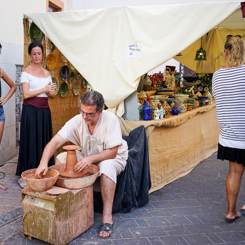 Pottemaker lager kjeramikk foran salgsbod i middelaldermarked i Nucia
