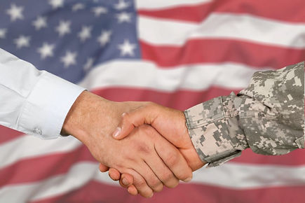 Two men shaking hands in front of an American flag. One is wearing military uniform, and the other is wearing a dress shirt.