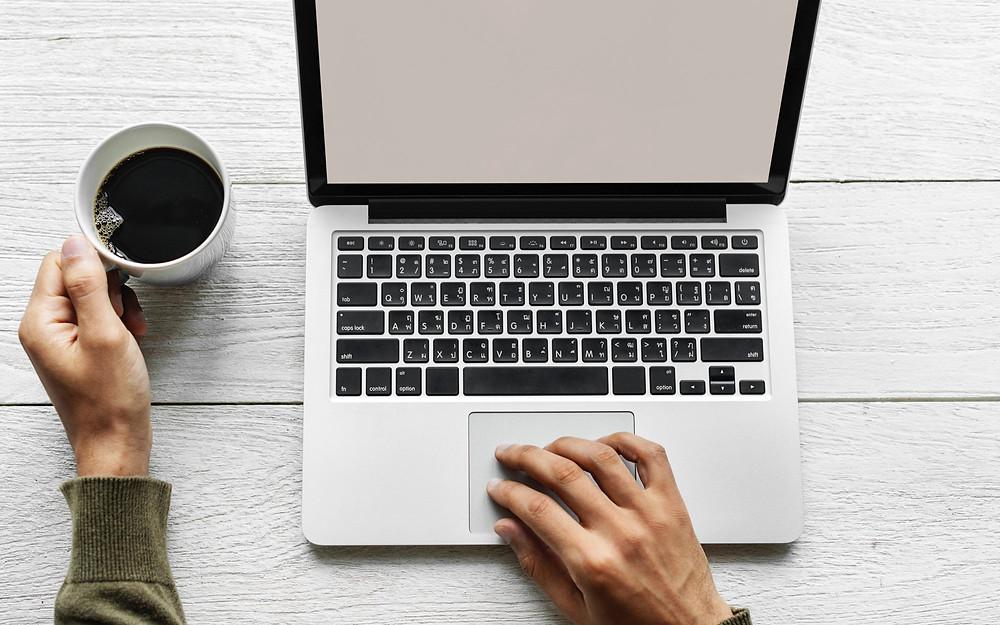 man drinking coffee working on macbook