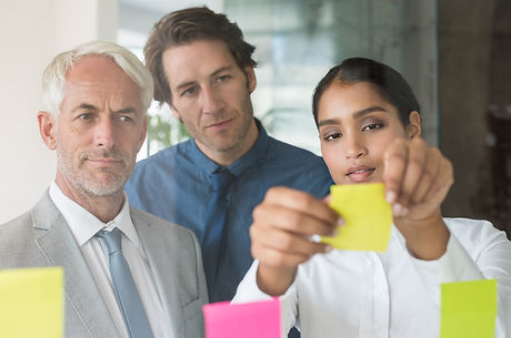 Multi ethnic young businesswoman sticking adhesive notes on glass wall in office. Close up of leader
