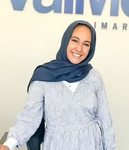 Female Office Manager in front of logo
