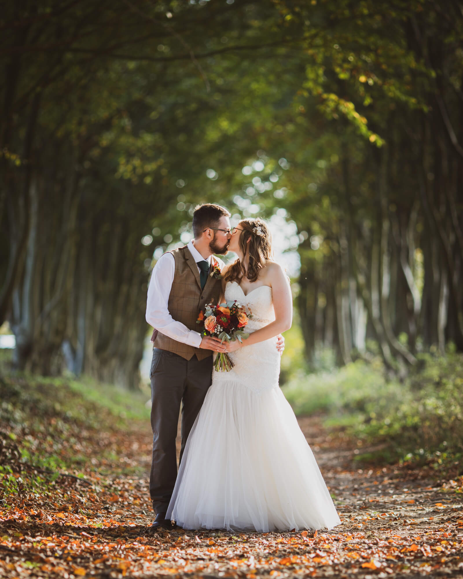 bride and groom kiss, in trees, Wiltshire wedding photographer