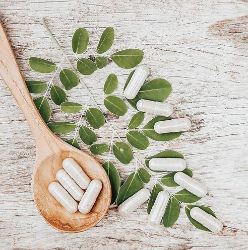 Herbal_capsules_on_moringa_leaf_with_woo