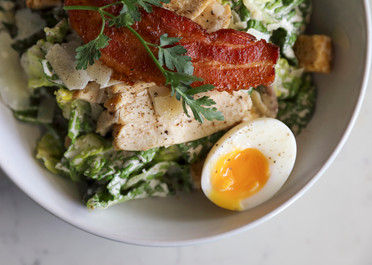 Close up food photography of soft boiled egg in chicken ceasar breakfast salad from Street Restaurant in bournemouth