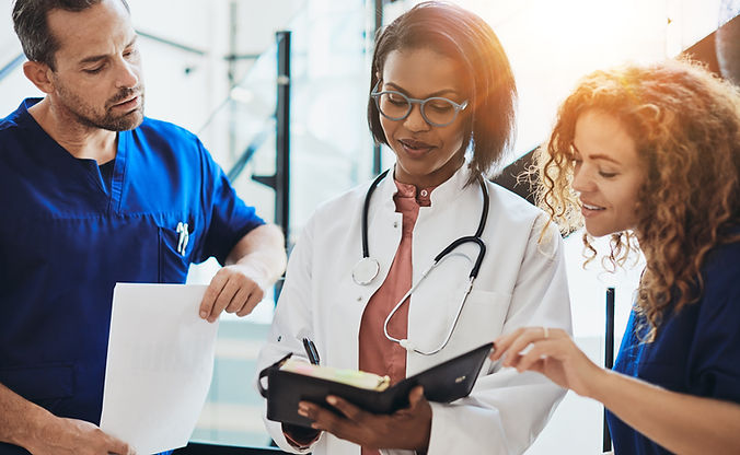 Medical team composed of two females and one male examining notes together.