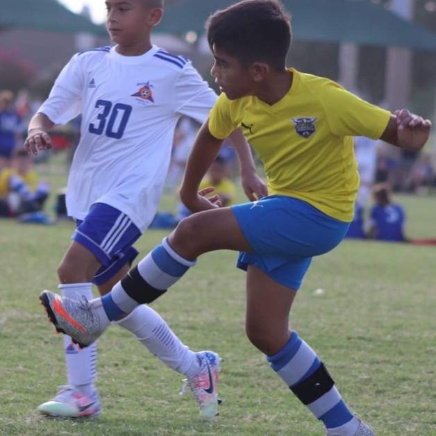 young vaquero kicking ball.jpeg