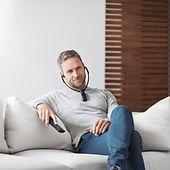 Sennheiser being worn by a man sitting on lounge enjoying TV