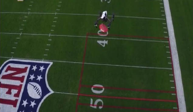 A DJI Inspire releases a football at the NFL Pro Bowl Skills Challenge