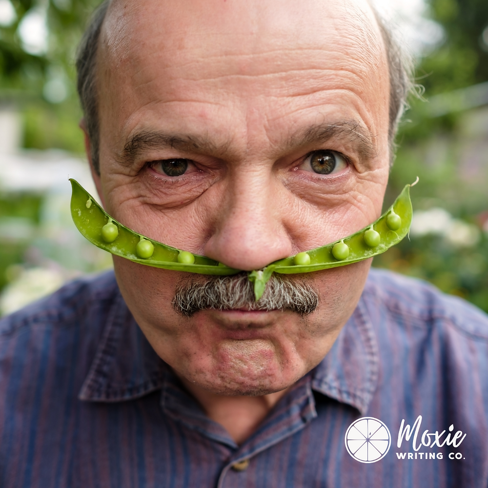 An older man making a silly face with a pea under his nose as a mustache