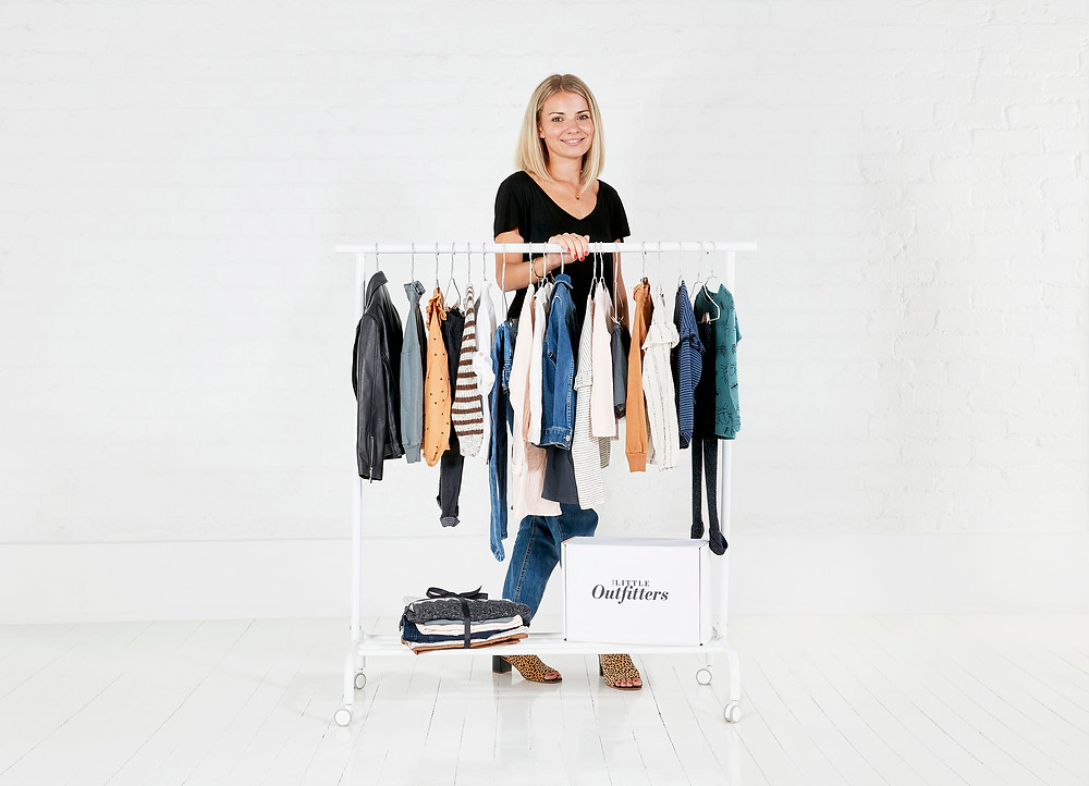 Lady standing next to a clothes rail