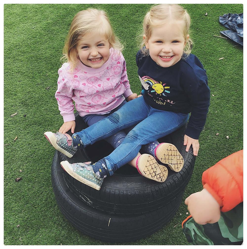 Children sat on a tyre in a playground