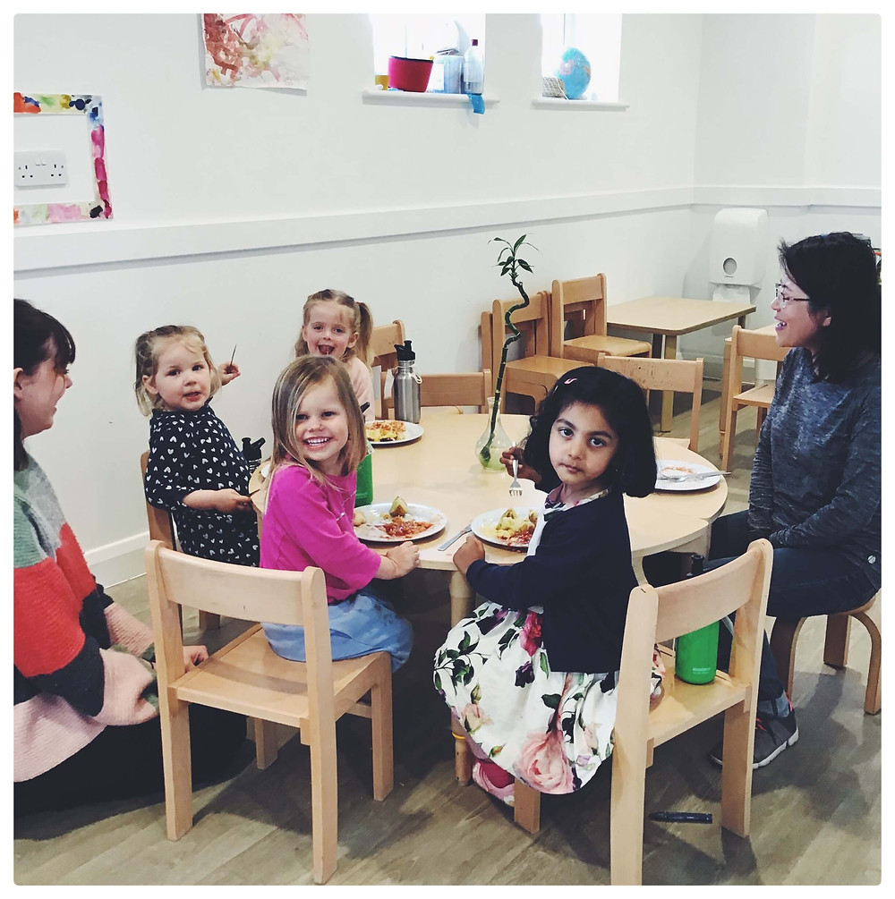 Children eating at a table with adults