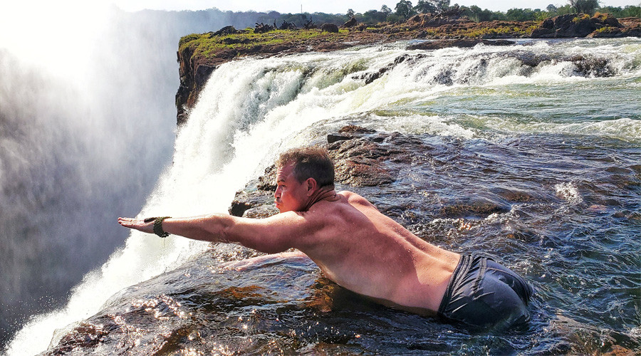 Kevin Larson of Denver, CO enjoys playing Superman at the edge of Victoria Falls