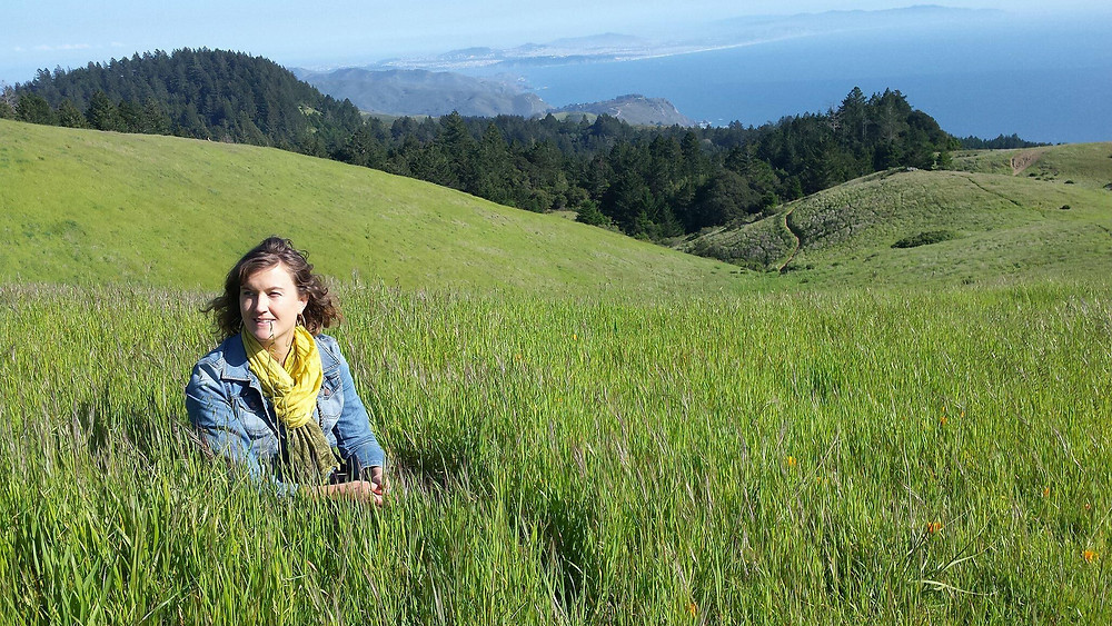 Our founder in a field with ocean view