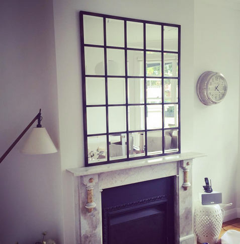 Large mirror above fire placed installed by a professional art hanger