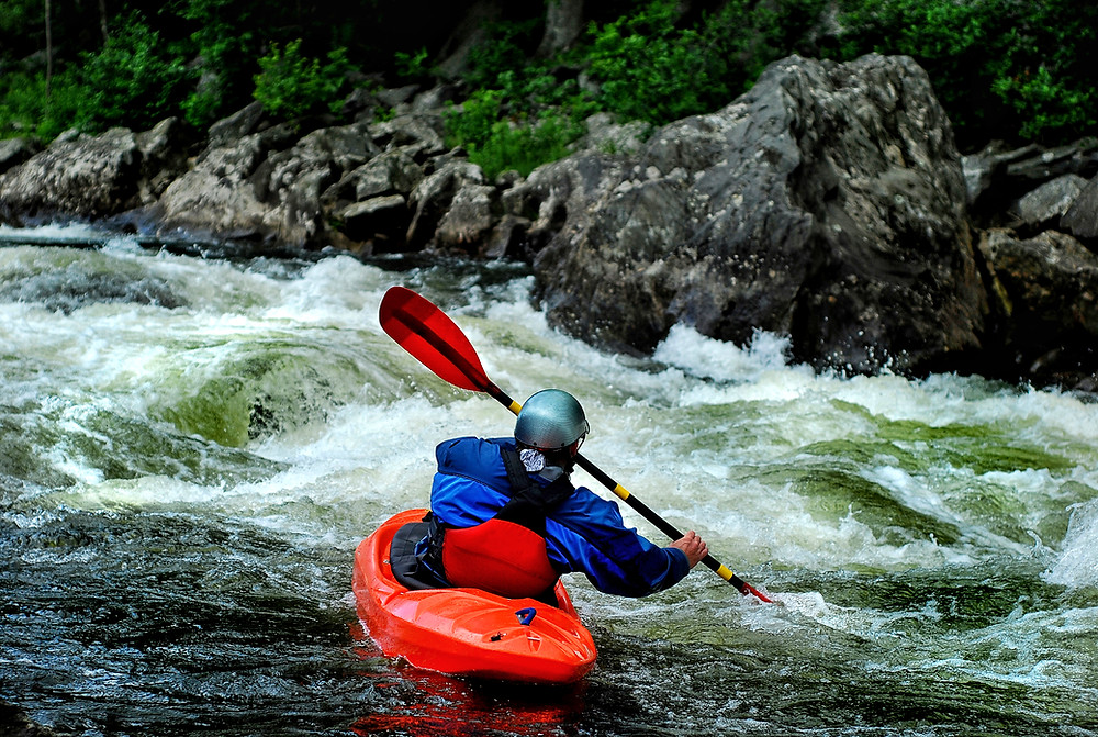 Kayaker eddying out on a whitewater river
