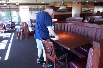A CSN client wipes down tables at his job.