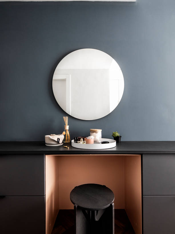 Round mirror on a bedroom wall