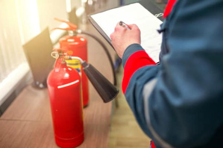 inspecting-fire-extinguishers-with-paper