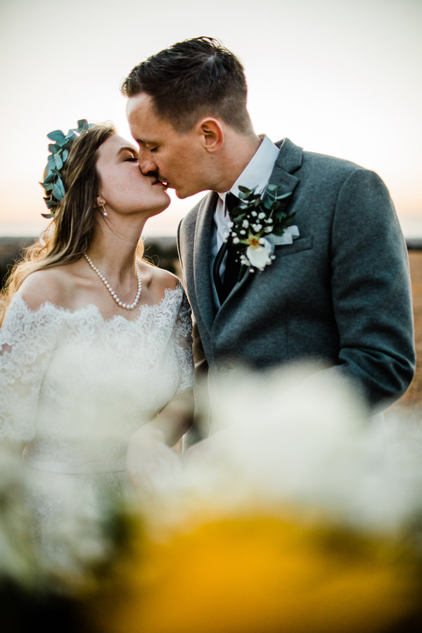 bride and groom kiss in flowers