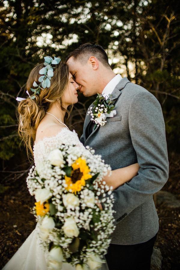 bride and groom moody kiss flowers