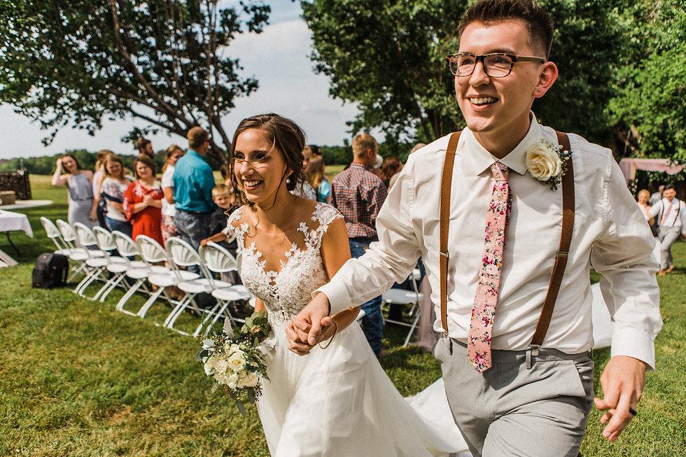 bride and groom run down aisle
