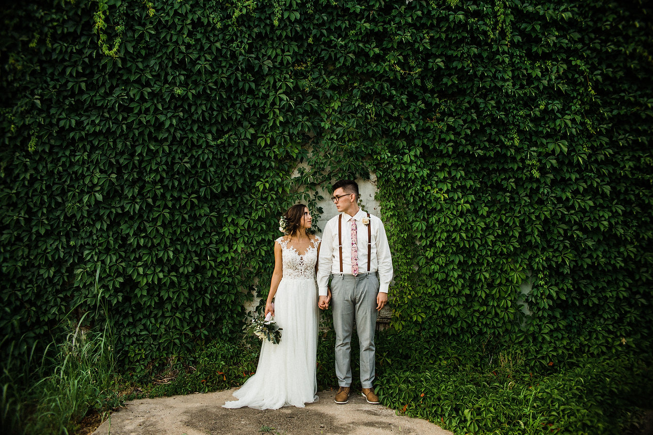 moody bride and groom green vines