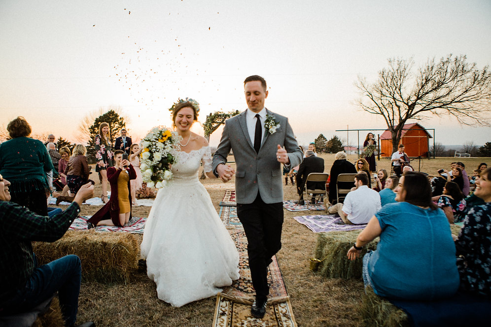 bride and groom running down aisle