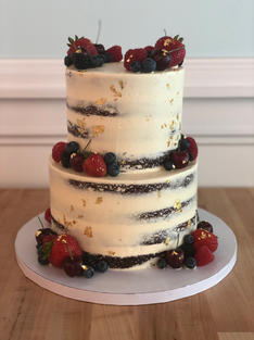 """4"""" & 6"""" $280 6"""" & 8"""" $280 7"""" & 10"""" $425  Your choice of Chocolate cake (pictured), or Vanilla iced in the """"naked"""" style so the cake layers show through.  Accented with gold leaf and finished with fresh fruit."""