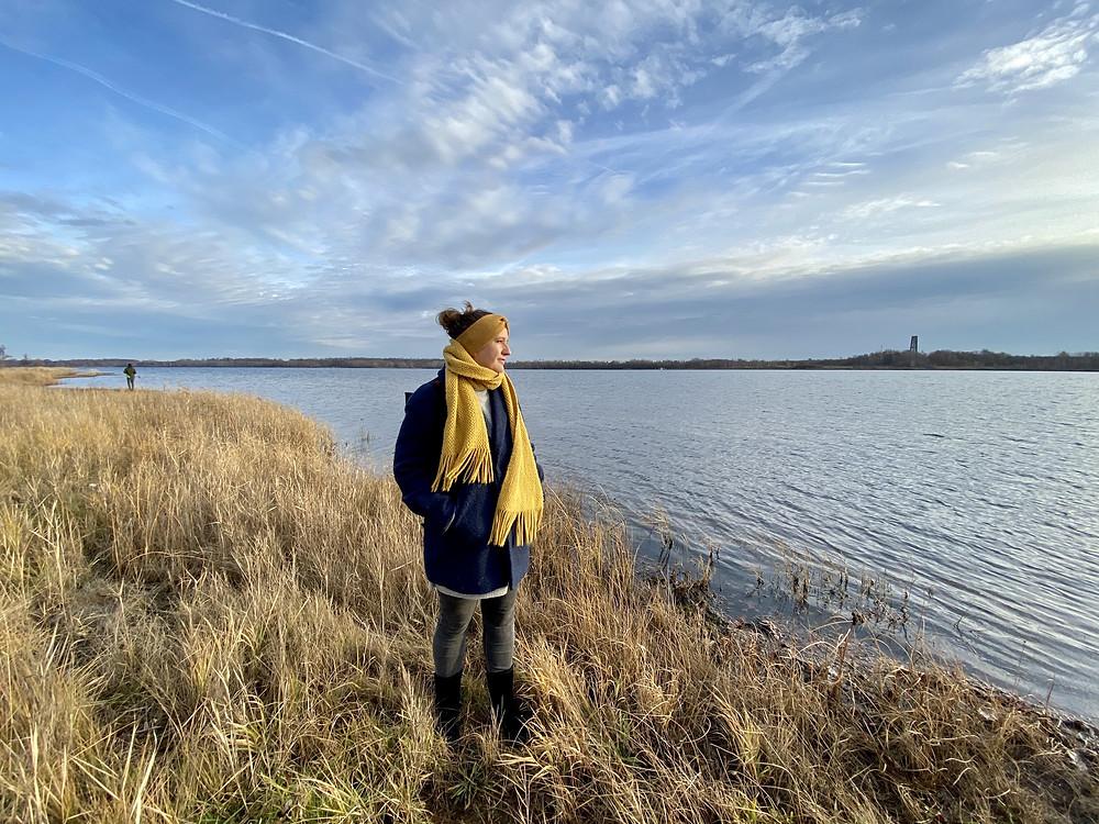 Junge Frau steht am See, blickt in die Weite, gelber Schal und Stirnband