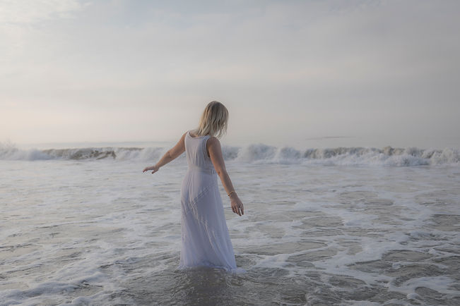 Carissa in the waves at the beach in LA where she sees clients struggling with stress utilizing an acceptance-based approach