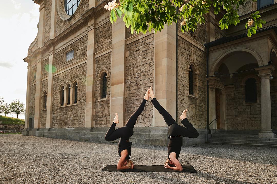 Susen und Andy von Yogagold vor der Kirche Enge beim Yoga machen. Holy Yoga wie sie das einzigartige Pop Up Yoga getauft haben.