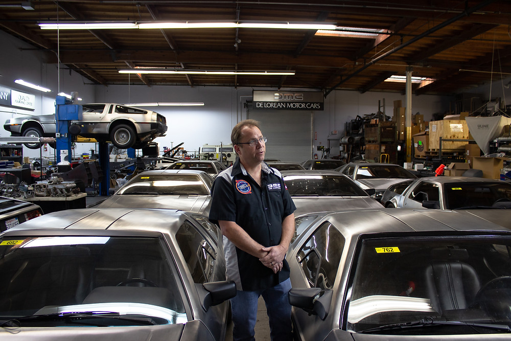 Danny Botkin standing in front of the collection of client cars.