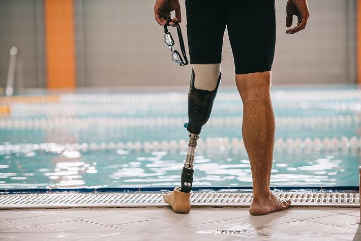 Homme à la piscine avec une prothèse de jambe