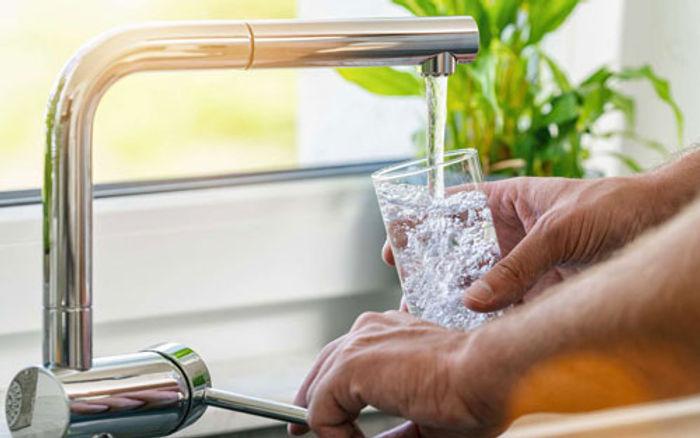 Homme qui se sert un verre d'eau au robinet