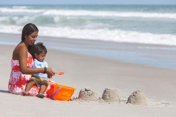 Une maman et son bébé jouent sur la plage.